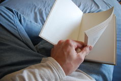 Hombre que lee un libro en cama Imagen de archivo libre de regalías