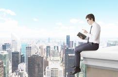 Hombre que lee un libro en el tejado Fotografía de archivo