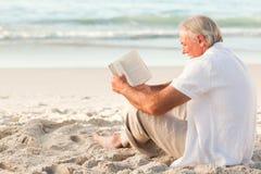 Hombre que lee un libro en la playa Foto de archivo libre de regalías