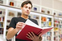 Hombre que lee un libro en una biblioteca Foto de archivo