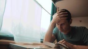 Hombre que lee un libro en un viaje largo del tren Viaje de tren del coche del concepto del viaje del ferrocarril Opinión de la f almacen de video