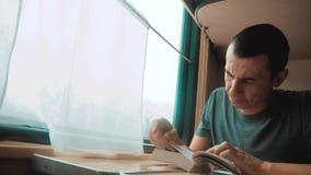 Hombre que lee un libro en un viaje largo del tren Viaje de tren del coche del concepto del viaje del ferrocarril visi?n hermosa  metrajes