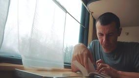 Hombre que lee un libro en un viaje largo del tren viaje de tren de la forma de vida del coche del concepto del viaje del ferroca almacen de metraje de vídeo