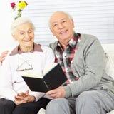 Hombre que lee un libro a la mujer mayor Imagen de archivo libre de regalías