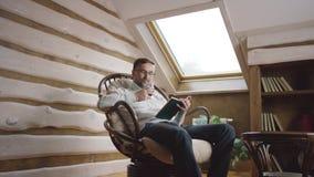 Hombre que lee un libro y que bebe el vino en el ático almacen de video