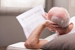 Hombre que lee un periódico en un sofá Foto de archivo libre de regalías