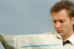 Hombre que lee un periódico en blanco Imagenes de archivo