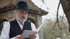 Hombre que lee una hacia fuera-alabanza del poema almacen de video
