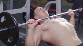 Hombre que levanta el barbell en el gimnasio metrajes
