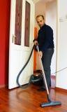 Hombre que limpia con la aspiradora Imagenes de archivo