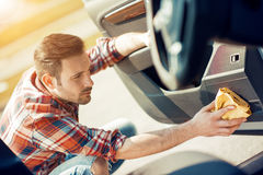 Hombre que limpia el interior de su coche imagen de archivo