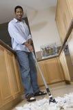 Hombre que limpia el piso con la fregona Foto de archivo