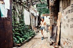 Hombre que limpia la calle fuera de su hogar en un hutong típico de la ciudad fotos de archivo