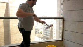 Hombre que limpia la cerca de aluminio del balcón de cristal decorativo exterior con una fregona telescópica de doble cara metrajes