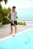 Hombre que limpia la piscina privada Imagen de archivo libre de regalías