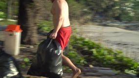 Hombre que limpia la playa almacen de metraje de vídeo