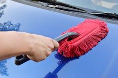Hombre que limpia un coche azul, Imagen de archivo