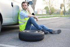 Hombre que llama el servicio de la ayuda para un neumático plano foto de archivo