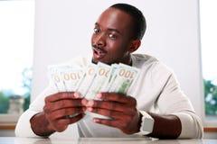 Hombre que lleva a cabo dólares de EE. UU. Fotos de archivo