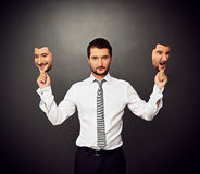 Hombre que lleva a cabo dos máscaras con diverso humor imagen de archivo