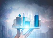 Hombre que lleva a cabo el holograma de la ciudad en ciudad de la noche fotografía de archivo