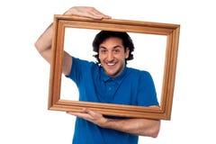 Hombre que lleva a cabo el marco de madera Imágenes de archivo libres de regalías