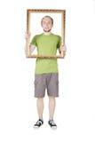 Hombre que lleva a cabo el marco decorativo Imagenes de archivo