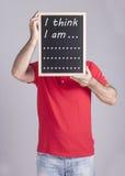 Hombre que lleva a cabo el mensaje escrito en una pizarra Fotografía de archivo