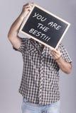 Hombre que lleva a cabo el mensaje escrito en una pizarra Imagenes de archivo