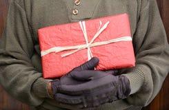 Hombre que lleva a cabo el regalo de Navidad Imagen de archivo libre de regalías