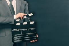 Hombre que lleva a cabo el tablero de chapaleta de la película en negro imágenes de archivo libres de regalías