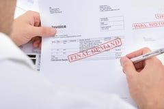Hombre que lleva a cabo la factura con la notificación de la demanda final Fotos de archivo libres de regalías