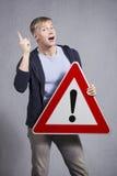 Hombre que lleva a cabo la señal de tráfico amonestadora con la marca de exclamación. Imagenes de archivo