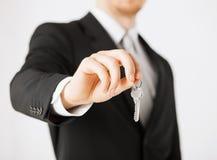 Hombre que lleva a cabo llaves de la casa Imagenes de archivo