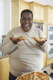 Hombre que lleva a cabo partes de la pizza y de la risa Imagen de archivo libre de regalías