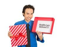 Hombre que lleva a cabo reforma de la atención sanitaria de la muestra en caja de regalo foto de archivo