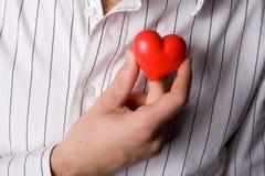 Hombre que lleva a cabo un corazón rojo imagen de archivo libre de regalías