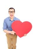 Hombre que lleva a cabo un corazón rojo grande Imágenes de archivo libres de regalías