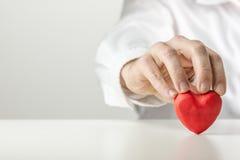 Hombre que lleva a cabo un corazón rojo simbólico de la tarjeta del día de San Valentín foto de archivo