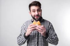 Hombre que lleva a cabo un pedazo de hamburguesa el estudiante come los alimentos de preparación rápida comida no útil individuo  Fotografía de archivo