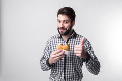 Hombre que lleva a cabo un pedazo de hamburguesa el estudiante come los alimentos de preparación rápida comida no útil individuo  Imágenes de archivo libres de regalías
