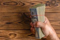 Hombre que lleva a cabo un puñado de 100 billetes de dólar Imagen de archivo