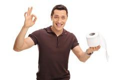 Hombre que lleva a cabo un rollo del papel higiénico Imagen de archivo libre de regalías
