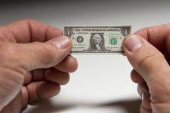 Hombre que lleva a cabo un un billete de dólar minúsculo Fotografía de archivo libre de regalías