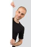 Hombre que lleva a cabo una muestra en blanco Imagen de archivo