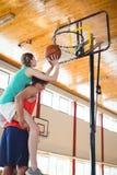 Hombre que lleva a cuestas al amigo femenino mientras que juega a baloncesto Fotografía de archivo libre de regalías