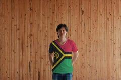 Hombre que lleva el color de la bandera de Vanuatu de la camisa y que se coloca con cruzado detr?s de las manos traseras en el fo imágenes de archivo libres de regalías