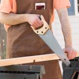Hombre que lleva el delantal de Brown y que asierra la madera imagenes de archivo