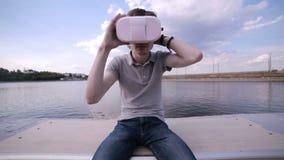 Hombre que lleva la ciudad del ina de las auriculares de VR Usando gestos con las manos almacen de metraje de vídeo