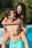Hombre que lleva a la mujer alegre por la piscina Fotos de archivo libres de regalías